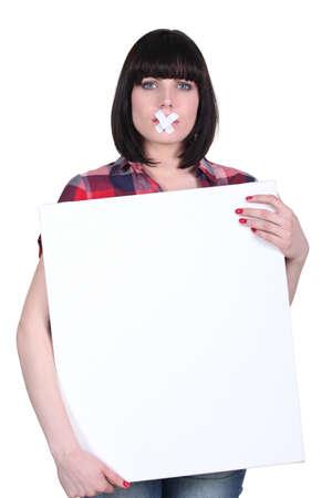 oppress: Woman with bandage on mouth holding panel Stock Photo