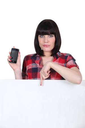 Woman with a smartphone and a board left blank for your message photo