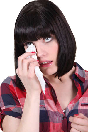 whining: Brunette with mote in the eye Stock Photo