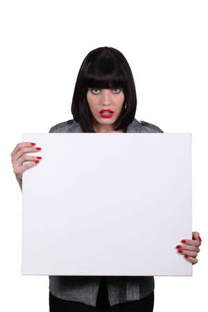 a woman looking amazed and showing a white panel Stock Photo - 13844605