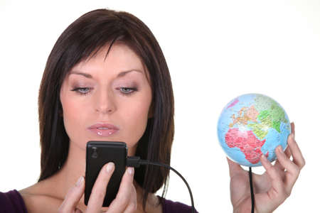woman charging battery of cell phone with globe photo