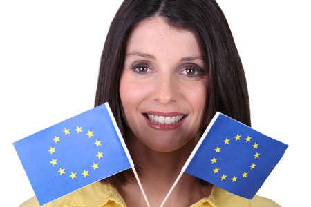 common market: Woman holding up European Union flags Stock Photo