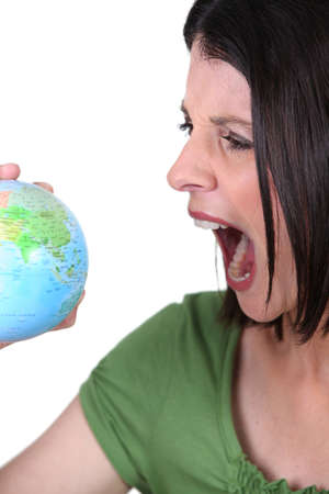 work worker workforce world: Angry woman with a globe Stock Photo