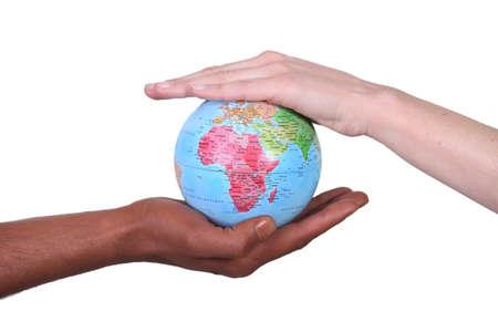 longitude: Two hands touching miniature globe Stock Photo