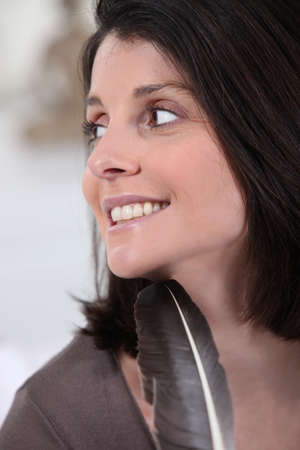 Woman smiling with a feather photo