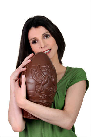 guilty pleasures: Woman with an enormous chocolate egg Stock Photo