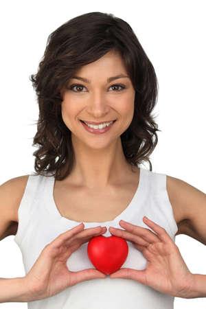 soppy: Brunette holding heart-shaped object Stock Photo