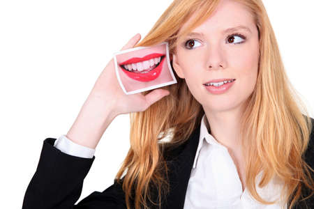Young woman holding a picture of a mouth to her ear photo