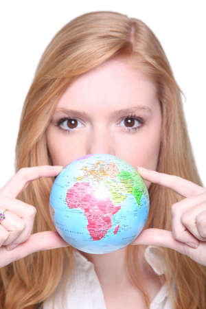 Woman hiding her mouth with a mini-globe photo