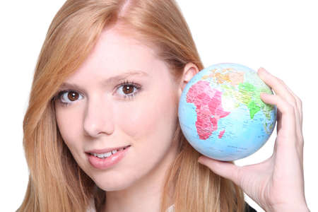 world at your fingertips: Ginger haired teen holding miniature globe Stock Photo