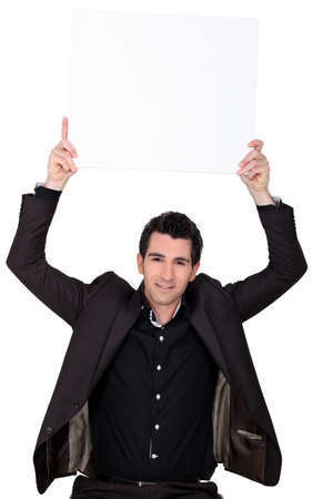 Businessman holding up blank advertising panel Stock Photo - 13847975