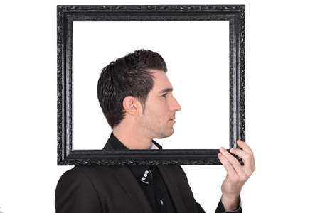 cocky: Man holding up a picture frame around his head Stock Photo