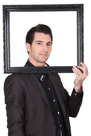 sideways glance: Man posing behind an empty picture frame Stock Photo