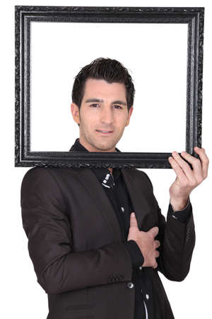 young businessman looking through a picture frame photo