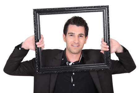 self conceit: Man holding empty picture frame Stock Photo