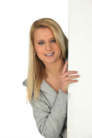 Young woman peeking out from behind a wall Stock Photo - 13849402