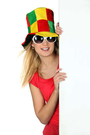 Young woman in a mad hat with a board left blank for your message photo