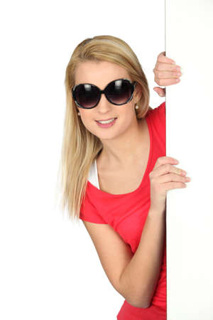 incarnate: Blonde woman behind white wall Stock Photo