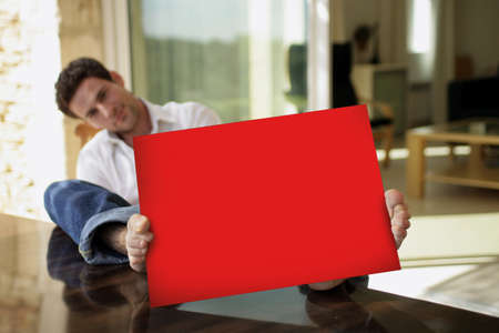 Man sat on his patio with red poster photo