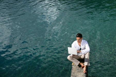 business man laptop: El hombre emplazamiento sobre el agua con un ordenador port�til Foto de archivo