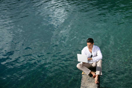 Man siting over water with a laptop photo
