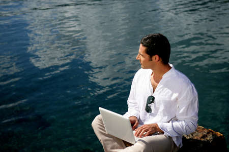 Man using his laptop by the waters edge photo