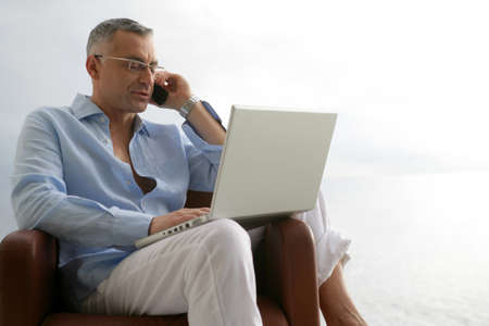 Relaxed man with a laptop and phone photo