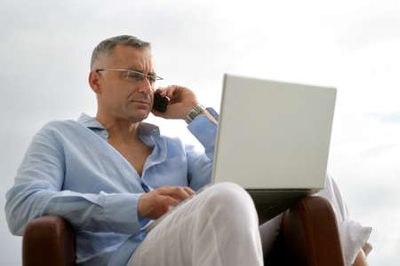 Man with a laptop and phone outdoors photo