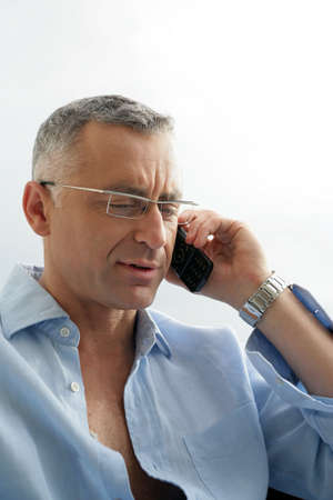 grey haired: Grey haired man speaking on his mobile