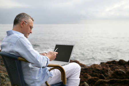 Man on a chair at the beach with his laptop photo