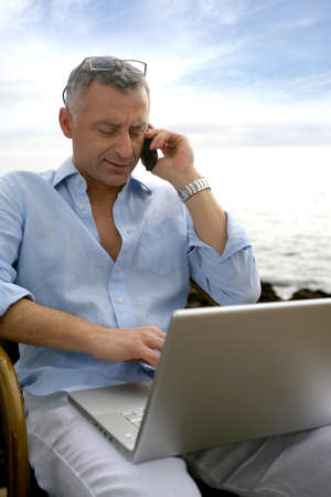 businessman on vacation working on his laptop and talking on his cell photo