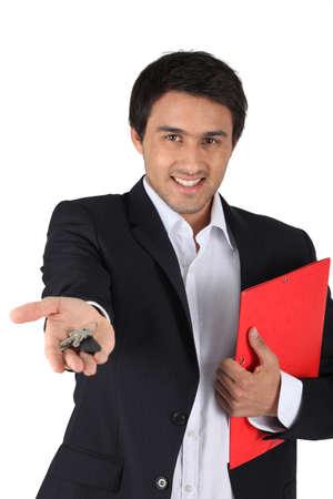 Estate-agent handing over keys to house photo