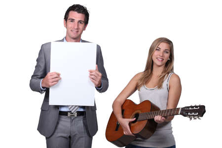 Teenage girl playing guitar teacher holding blank message board photo
