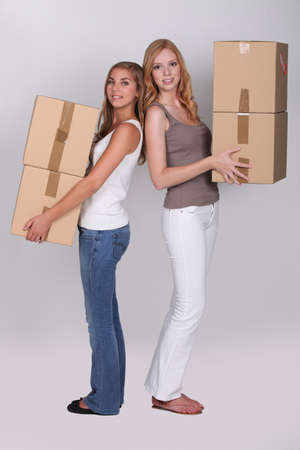Young women carrying cardboard boxes photo