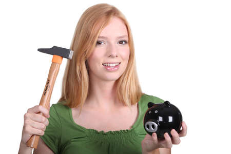 spendthrift: blonde with piggy-bank and hammer