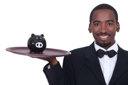 Waiter holding a piggy bank on his tray photo
