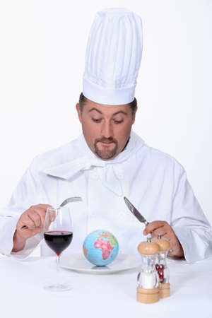 circumspect: a chef cook watching a little globe in his plate
