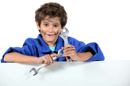 repairer: Little boy with mechanic clothing and tools Stock Photo