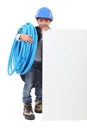 flexi: Young boy pretending to be a plumber with a board left blank for your message Stock Photo