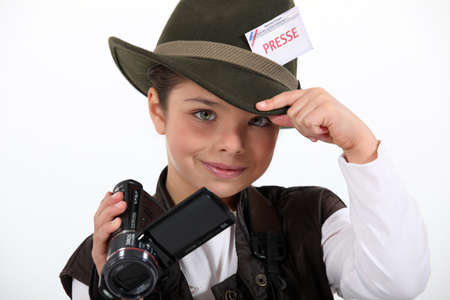 little girl taking a camera and wearing a costume of journalist photo