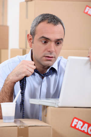 Panicking man using a laptop surrounded by boxes Stock Photo - 13867562