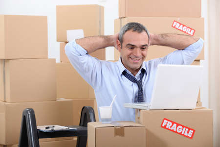 vacate: Man surrounded by cardboard boxes using his laptop