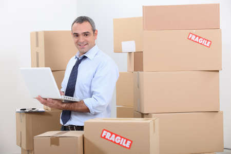 Man in suit surrounded by stacks of boxes photo