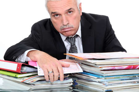 exasperate: Grey hairy man looking fed up in front of paper work