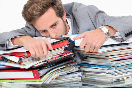 workaholic: Man drowning in stacks of paperwork Stock Photo