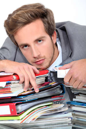 troublesome: young man lying down on a desk full of binders and notebooks