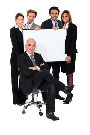 trading board: Four young executives holding a blank presentation board behind their boss Stock Photo