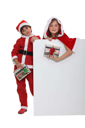 Children dressed up in Santa Claus costumes photo