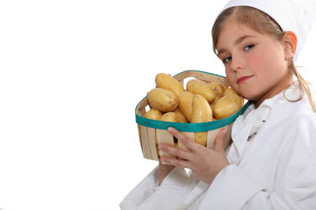 Little girl with a basket of new potatoes photo
