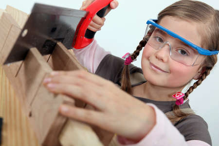 woodworking: Little girl using a hand saw Stock Photo